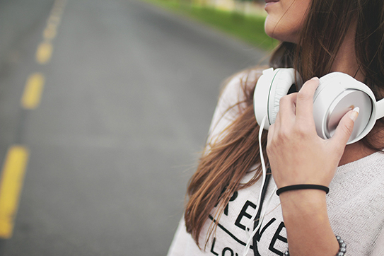 picture of a girl with headphones, standing on a road